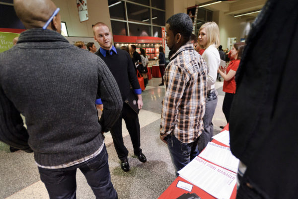 Photo of student talking with representatives from the retail company Buckle at the Spring Career and Internship Fair.